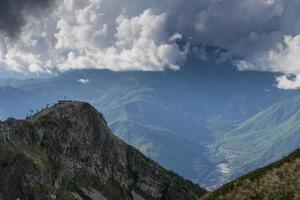 Paysage de tramway ou téléphérique menant à une ville entre les montagnes avec un ciel bleu nuageux photo