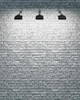 mur de briques blanches avec trois projecteurs