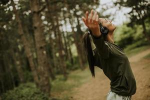 jeune femme avec des écouteurs preading ses bras dans la forêt parce qu'elle aime s'entraîner à l'extérieur