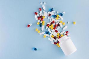 Pilules colorées tombent d'une bouteille en plastique sur fond bleu photo