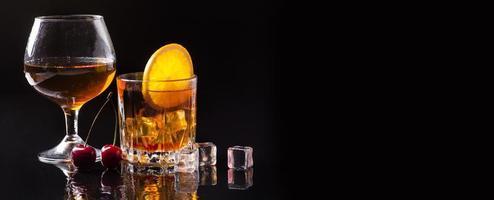 Vue avant du whisky avec du cognac orange en verre avec copie espace photo