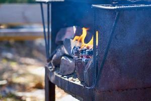 Feu dans un gril vintage rouillé en plein air avec arrière-plan flou