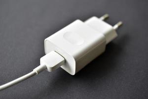 chargeur de téléphone portable blanc sur fond noir photo