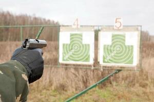 deux cibles et un bras tenant une arme à feu photo