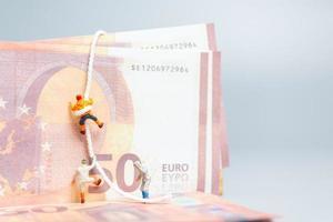 personnes miniatures, grimpeur grimpe sur un billet en euros, concept d'entreprise. photo