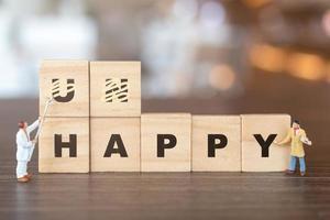 Gens miniatures, équipe de travailleurs sur des blocs de bois avec le mot mécontent du préfixe non barré, laissant le mot heureux photo