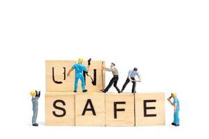 Personnes miniatures, équipe de travailleurs changeant le mot dangereux transformé en coffre-fort sur fond blanc photo
