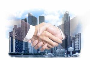 Double exposition d'hommes d'affaires poignée de main sur un quartier financier de construction de la ville moderne et le commerce, partenariat commercial réussi et concept de plan stratégique