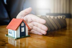 gros plan femme d'affaires avec la main entre une maison et des blocs de bois, arrêtant le risque de tout, sécurité et concept d'assurance.