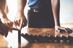 concept de gestion des risques commerciaux. équipe commerciale arrêtant des briques en bois ensemble. photo