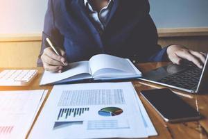 femme d'affaires ou comptable mains tenant un stylo avec un ordinateur portable, un compte et un concept d'épargne. photo