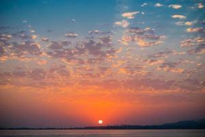 Coucher de soleil coloré dans un ciel nuageux sur un plan d'eau photo