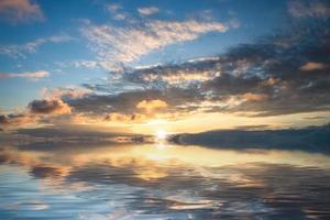 Coucher de soleil nuageux coloré sur un plan d'eau photo