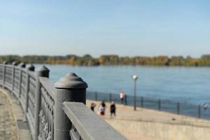Paysage urbain d'une clôture métallique à côté d'un plan d'eau avec des gens flous en arrière-plan et un ciel bleu clair à Irkoutsk, Russie photo