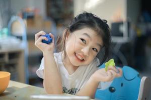 une charmante petite fille sourit largement tout en tenant des jouets dans ses mains. photo