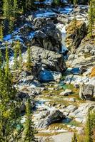 la neige fond sur un flanc de montagne rocheux photo