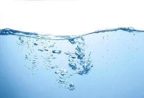 Nettoyer la surface de l'eau bleue avec des bulles et des éclaboussures sur fond blanc photo
