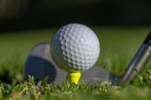Balle de golf blanche sur un tee jaune avec club photo