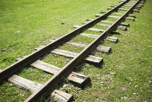 Chemin de fer à coucou abandonné entouré d'herbe verte. chemin de fer à coucou cassé. photo