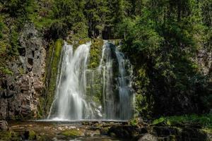 belle cascade descendant une paroi rocheuse verte photo