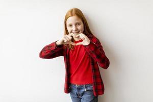 Jolie petite fille aux cheveux roux debout près du mur blanc et montrant la forme du coeur avec les doigts photo