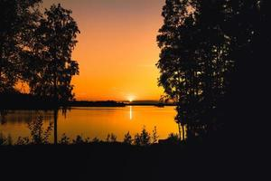 Beau coucher de soleil orange sur un lac en Suède photo