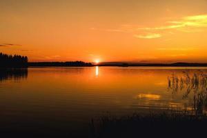 Beau coucher de soleil orange vif sur un lac en Suède photo