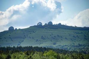 Paysage avec des bâtiments géométriques sur des collines verdoyantes avec un ciel bleu nuageux à Yalta, Crimée photo