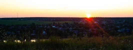 panorama surplombant le village et le soleil mourant au coucher du soleil. photo