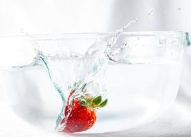 fraise éclaboussant dans l'eau photo