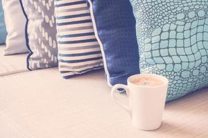 Tasse à café blanche sur canapé avec décoration d'oreiller photo