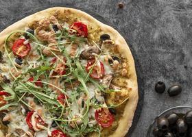 pizza traditionnelle avec garniture de roquette photo