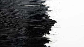 Coup de pinceau de peinture noire texturée artistique sur fond blanc photo