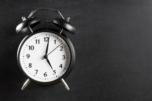 Réveil montrant 5 heures sur fond noir photo