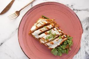 Poulet grillé, riz et salade de légumes frais sur table photo