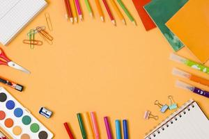 arrangement de fournitures scolaires encadré sur fond orange photo