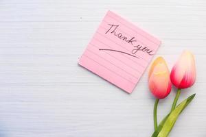 Merci pense-bête avec des tulipes sur fond blanc photo