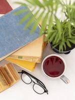 concept de lecture du matin avec thé chaud, verres et livres photo
