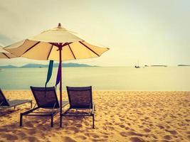 parasol et chaise sur la plage tropicale mer et océan au lever du soleil photo