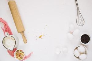 ingrédients de cuisson près du rouleau à pâtisserie au fouet photo