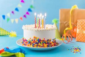 gâteau décoratif avec bougie allumée sur fond bleu photo