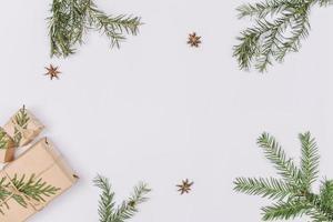 branches de sapin avec des cadeaux formant un cadre photo
