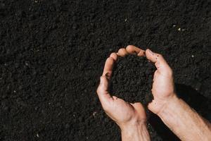 mains à plat tenant de la terre photo