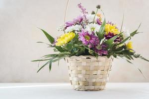 Panier en osier de composition de fleurs sur la table photo