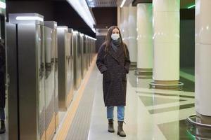 Une femme dans un masque médical attend l'arrivée d'un train dans le métro photo