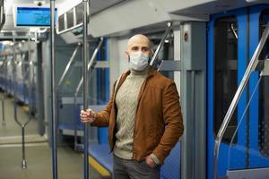 Un homme chauve avec une barbe dans un masque facial tient la main courante dans une voiture de métro photo