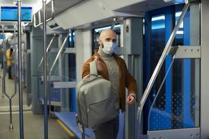 Un homme chauve avec une barbe dans un masque facial met un sac à dos dans une voiture de métro photo