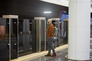 Un homme dans un masque facial tient un smartphone en attendant une rame de métro photo