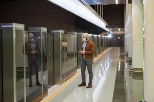 un homme avec un masque facial fait défiler les actualités en attendant une rame de métro photo