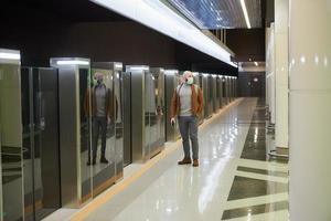 Un homme dans un masque facial utilise un smartphone en attendant une rame de métro photo
